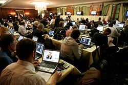 """Δημοσιογράφοι σε συνέντευξη τύπου. Οι εφημερίδες και τα blogs συχνά απαιτούν τα κυριότερα σημεία δηλώσεων και απαντήσεων να μεταδίδονται """"ζωντανά"""" από τους δημοσιογράφους που καλύπτουν την εκδήλωση."""